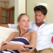 Couple sitting on sofa watching TV — Stock Video