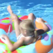 Girl lying on inflatable rubber ring floating in swimming pool and revolving. - Stock Photo
