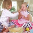 Two girls  tasting cake mixture - Stok fotoğraf