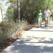 Senior couple holding hands as they walk along country path. — Stock Video #25307249