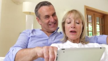 Happy couple relaxing on sofa with digital tablet. — Stock Video