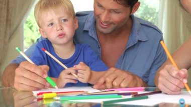 Father helping son as camera pans around to mother and daughter working on picture with pens together. — Stock Video