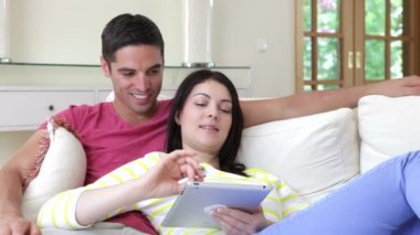 Happy couple relaxing on sofa and operate digital tablet — Stock Video