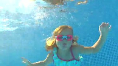 Underwater view young girl wearing goggles swims — Stock Video