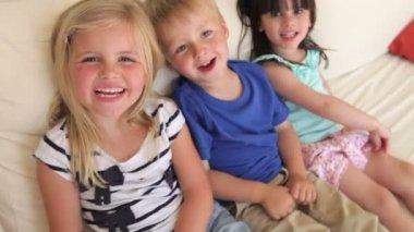 Group of three children sit on sofa — Stock Video