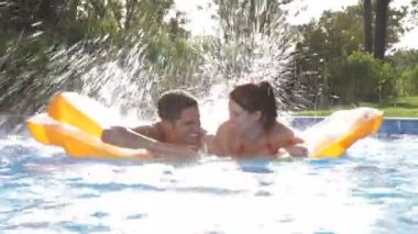 Couple lying on inflatable airbed in swimming pool — Stock Video