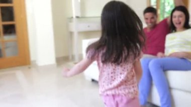 Parents sit on sofa as little girl runs into room to join them . — Stock Video