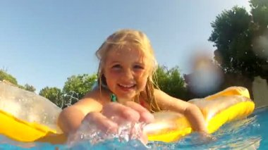 Girl lying on inflatable airbed in splashing camera position. — Stock Video