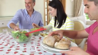 Couples seated around dining table serving food. — Stock Video