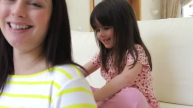 Little girl sits on sofa brushing mother's hair — Vidéo