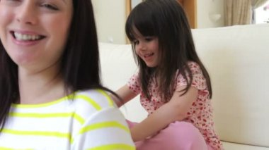 Little girl sits on sofa brushing mother's hair — 图库视频影像