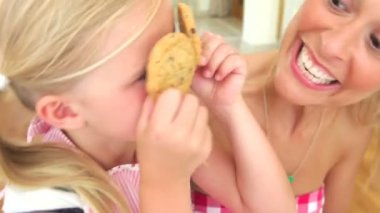 Daughter holds up two cookies over eyes — Stock Video