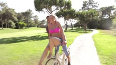 Man giving woman ride on handlebars as they cycle — Stock Video