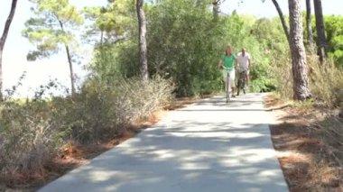 Romantic senior couple cycling along country path — Stock Video