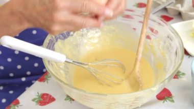 Senior woman breaking egg into bowl and then whisking into mixture. — Stock Video