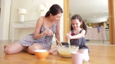 Mother and daughter sitting on floor adding ingredients into bowl and mixing. — Stock Video