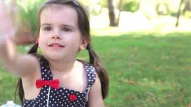 Chica se sienta en la alfombra en campo e intenta atrapar burbujas sopladas — Vídeo de Stock