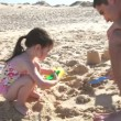 Stock Video: Father helping daughter as she makes sandcastle.