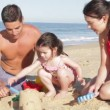 Family sitting on beach as daughter makes sandcastle with parents help — Stock Video