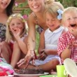 Children sitting on table eating chocolate cake with hands - mums join in. — Vidéo