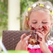 Stock Video: Girl sitting at table eating large messy slice of chocolate cake