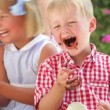 Royalty-Free Stock Векторное изображение: Children sitting at table eating melted chocolate with hands and talking with friends.