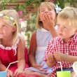 Children sitting at table eating jelly with hands and talking with friends.  — Stock Video