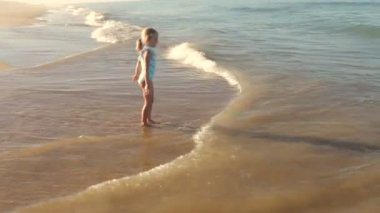 Young girl running away from waves as they break onto the shore. — Stock Video