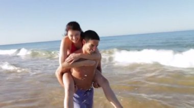 Man carries woman along shore on his back — Stock Video