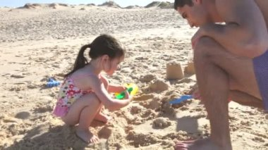 Father helping daughter as she makes sandcastle. — Stockvideo