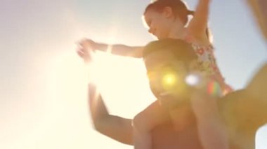 Looking up at daughter as father spins her around on his shoulders. — Stock Video