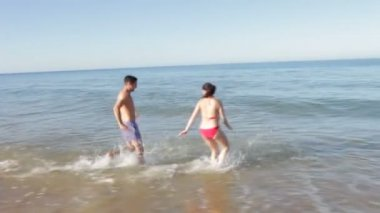 Couple run into sea before splashing one another. — Stock Video
