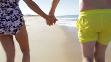 Senior couple as they walk along beach holding hands. — Stock Video
