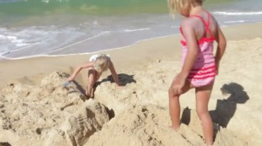 Two young girls building sandcastle with moat on beach. — Stock Video