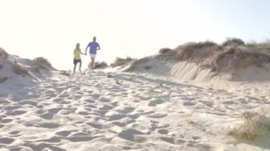 Senior couple in casual clothing running down sand dune — Stock Video
