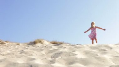 Girl in pretty dress running down sand dune — Stock Video