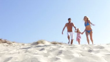 Family in swimwear running down sand dune — Stock Video