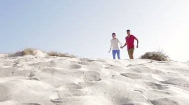 Couple in casual clothing running down sand dune — Stock Video