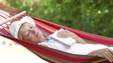 Senior woman rocking in hammock with eyes closed and book resting on her chest — Stock Video