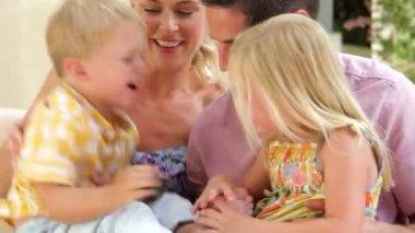 Madre y padre relajante en el asiento al aire libre con los niños. — Vídeo de Stock