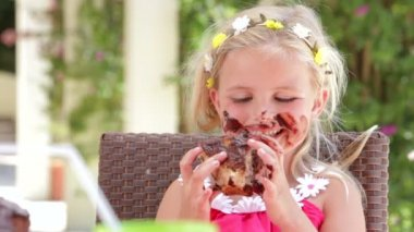 Girl sitting at table eating large messy slice of chocolate cake — Stock Video