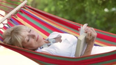 Senior woman rocking in hammock turning pages of book. — Stock Video