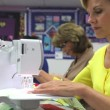 Woman sitting at bench operating electric sewing machine and cutting thread on garment. — Stock Video