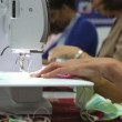 Woman feeding material through sewing machine. — Stock Video #25396649