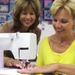 Stock Video: Womsitting at bench being shown how to operate electric sewing machine by tutor.