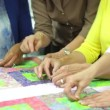 Stock Video: Working on quilt up to women being taught by teacher.