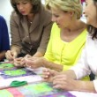 Stock Video: Women working on quilt being taught by teacher.
