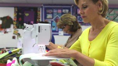 Mujer sentada en el banco opera la máquina de coser eléctrica e hilo de corte en la ropa. — Vídeo de stock