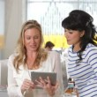 Two female colleagues talking and using digital tablet with busy office in background. — Stock Video #25400481