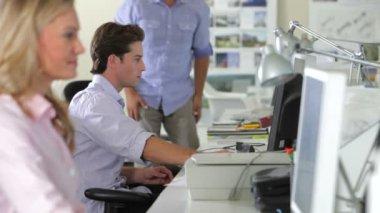 Uomo d'affari arriva e si siede sulla scrivania del collega maschio più giovane e discutono la visualizzazione sul computer. — Video Stock